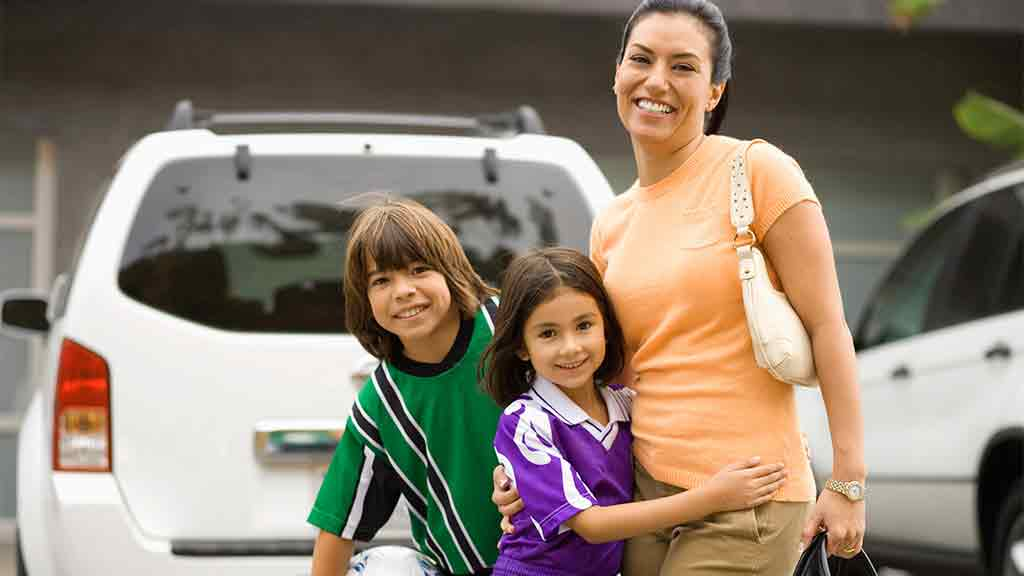 mother and two kids in front of car