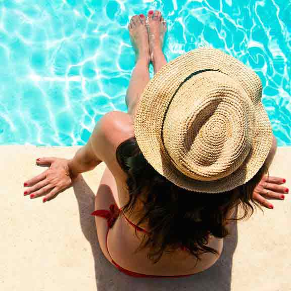 woman sits by pool square