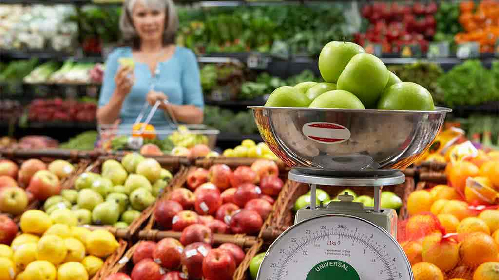 apples on scales at fruit and vegetable shop
