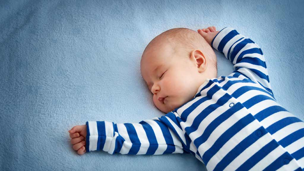 young baby asleep on bed