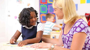 teacher talking with child in classroom