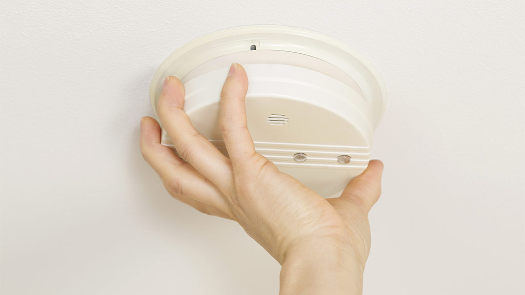 hand screwing in smoke alarm