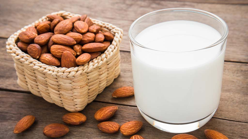 almonds and milk on wooden board alternative