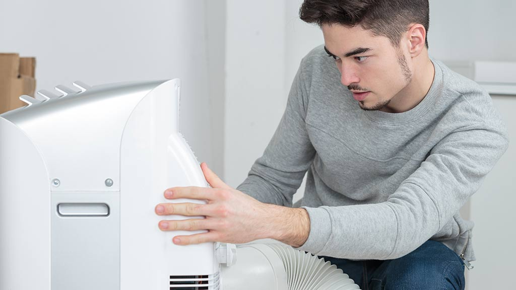man using a portable air conditioner at home