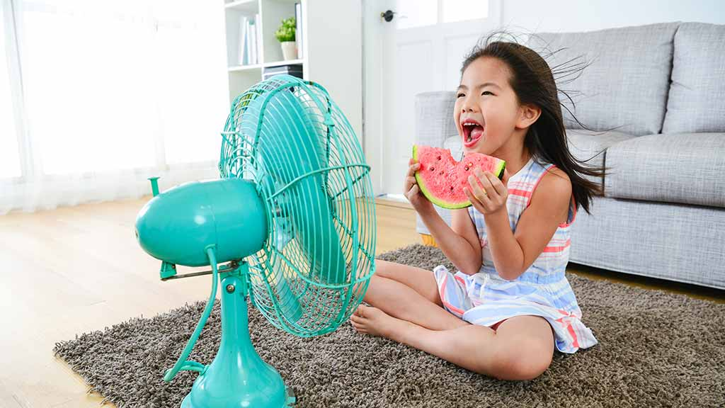 young girl sitting in front of electric fan