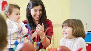early childhood educator claps child