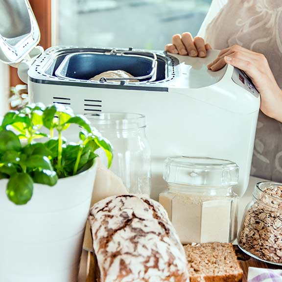woman using bread maker at home sq