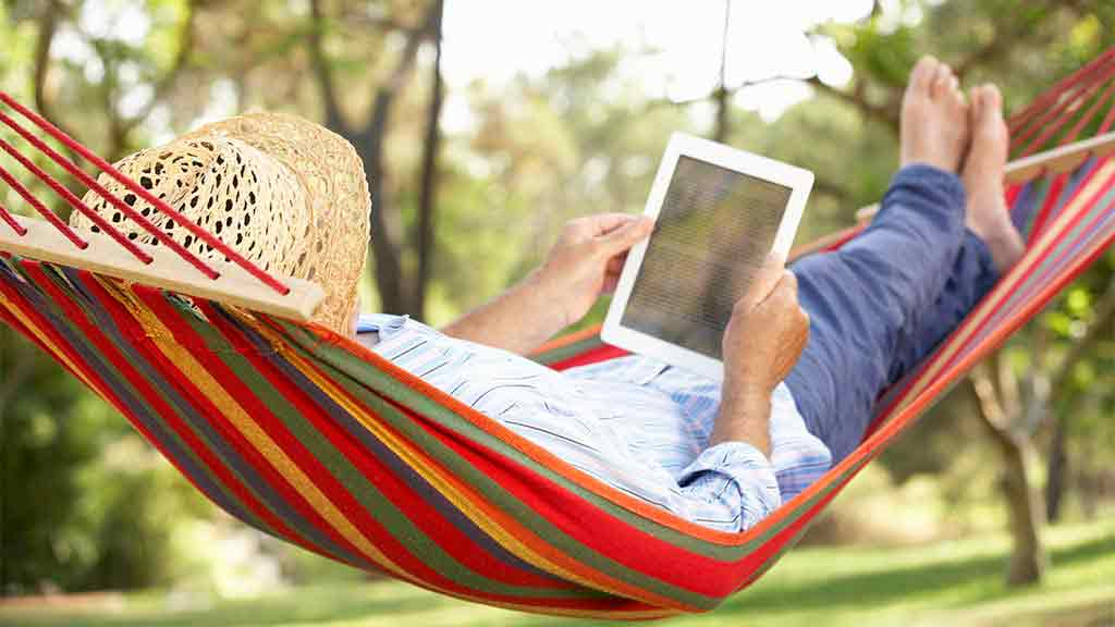 person using tablet on hammock