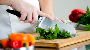 person using knife utensil to chop parsley