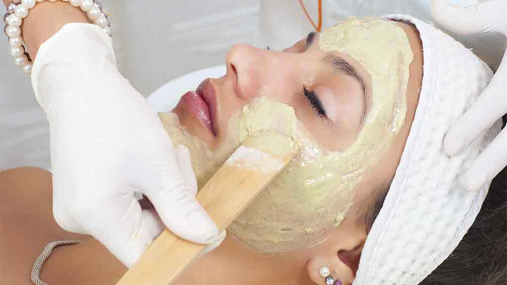 woman having cosmetic mask applied