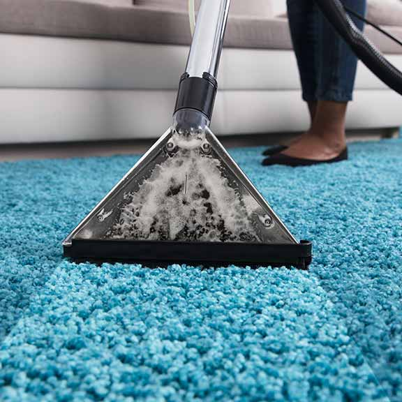 person using an at home carpet cleaner sq