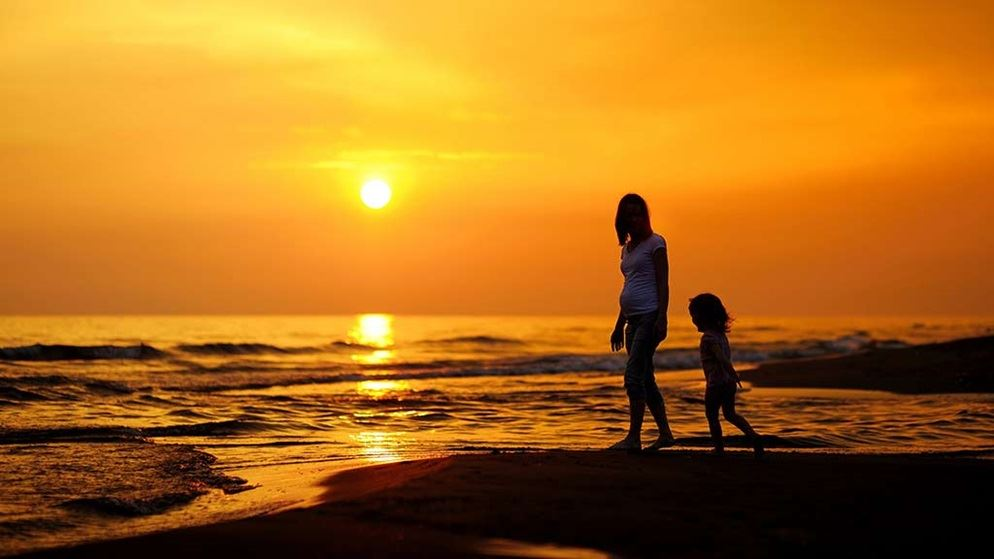 pregnant mother and daughter on gold coast beach