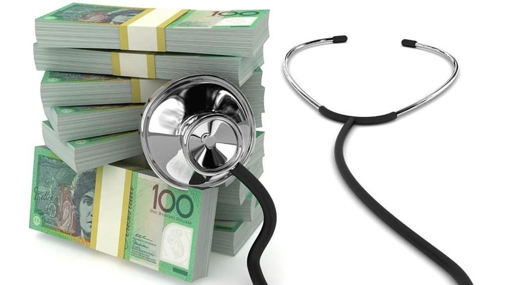 Stethoscope next to a bundle of one hundred dollar bills
