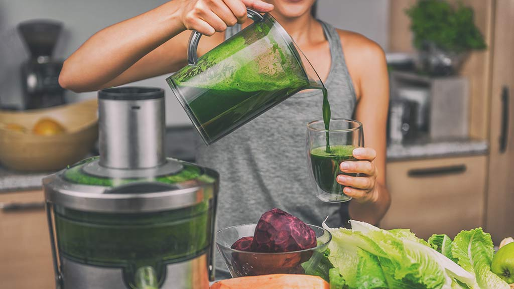 woman using juicer to make green juice