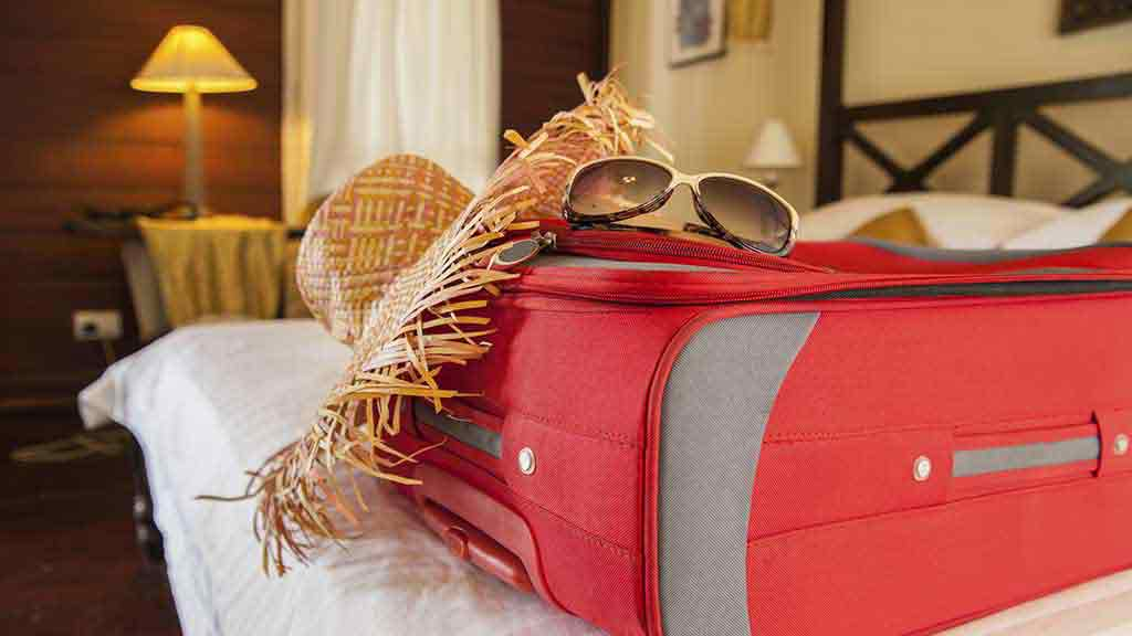 suitcase hat sunglasses on bed