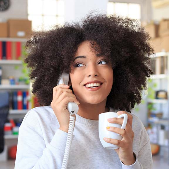young woman using landline phone sq